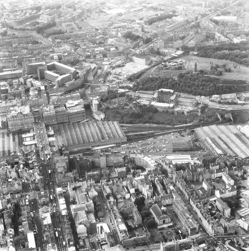 Oblique aerial view of centre of Edinburgh centred on St. Andrew's House, boiler house, and including St James' Centre and New Town at top of photograph, Royal High School to right, Cowgate at bottom and Waverley Station to left.