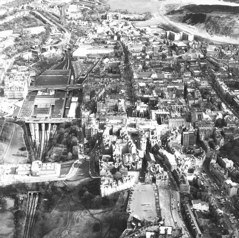 Aerial view of centre of Edinburgh including Castle Esplanade in foreground, looking down High Street towards Holyrood Palace, with The Mound and National Gallery of Scotland on left of photograph and Old College and Chambers Street on right