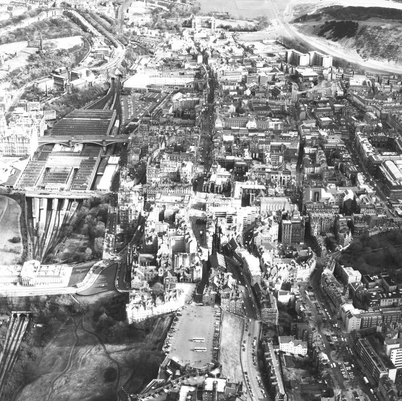 Aerial view of centre of Edinburgh including Castle Esplanade in foreground looking down High Street towards Holyrood Palace, with The Mound and National Gallery of Scotland on left of photograph and Old College and Chambers Street to right