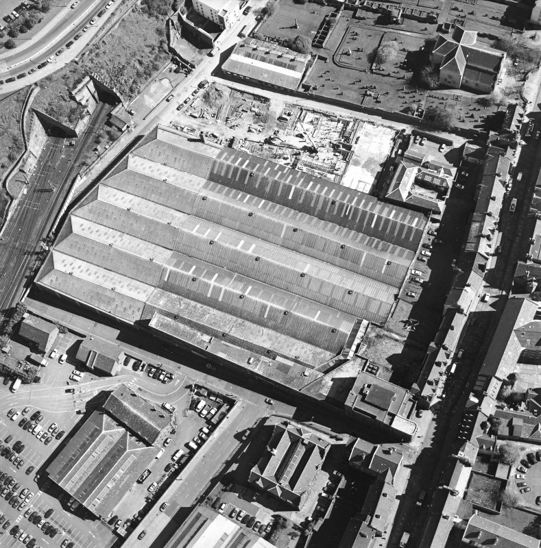 Oblique aerial view centred on the garage with the church and graveyard, New Street, Tolbooth Wynd and the Canongate adjacent, taken from the SW.