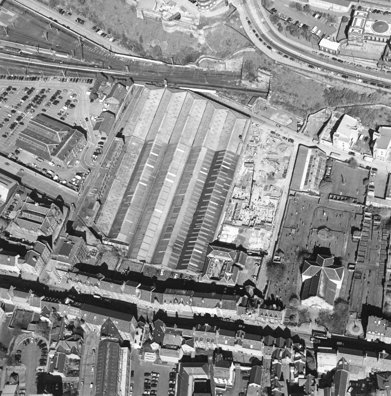 Oblique aerial view centred on the garage with the church and graveyard, New Street, Tolbooth Wynd and the Canongate adjacent, taken from the SE.