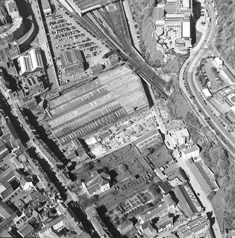 Oblique aerial view centred on the garage with the church and graveyard, New Street, Tolbooth Wynd and the Canongate adjacent, taken from the E.