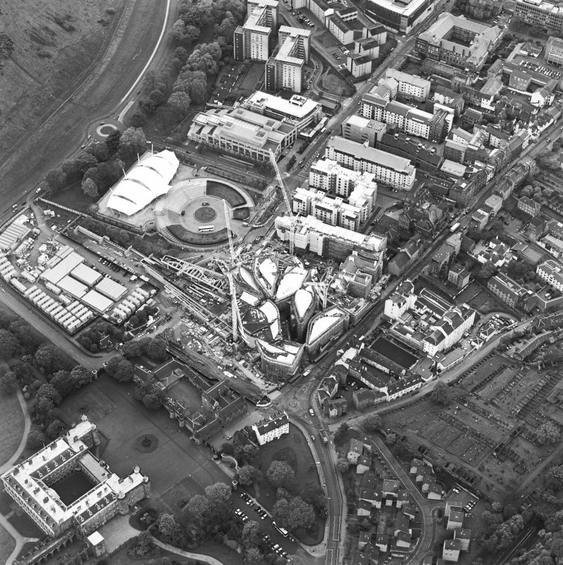 Oblique aerial view centred on the construction of the Scottish Parliament with exhibition centre adjacent, taken from the NNW.
