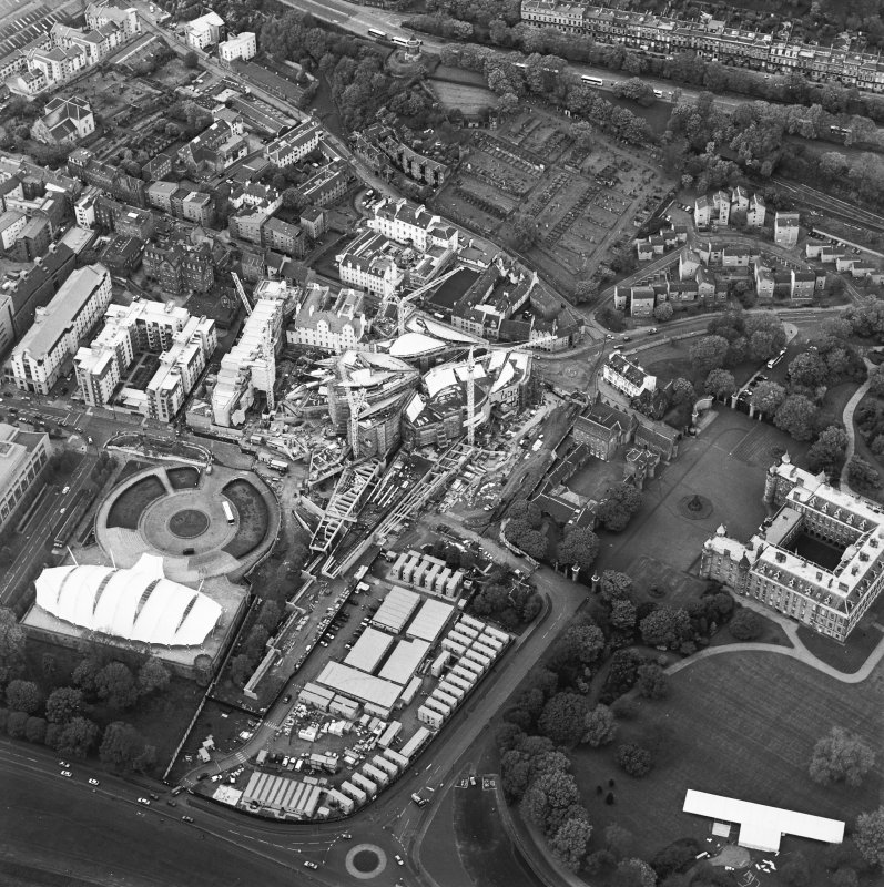 Oblique aerial view centred on the construction of the Scottish Parliament with exhibition centre adjacent, taken from the SE.