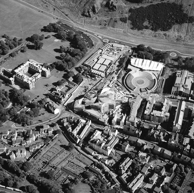 Oblique aerial view centred on the construction of the Scottish Parliament with the exhibition centre and palace adjacent, taken from the NW.