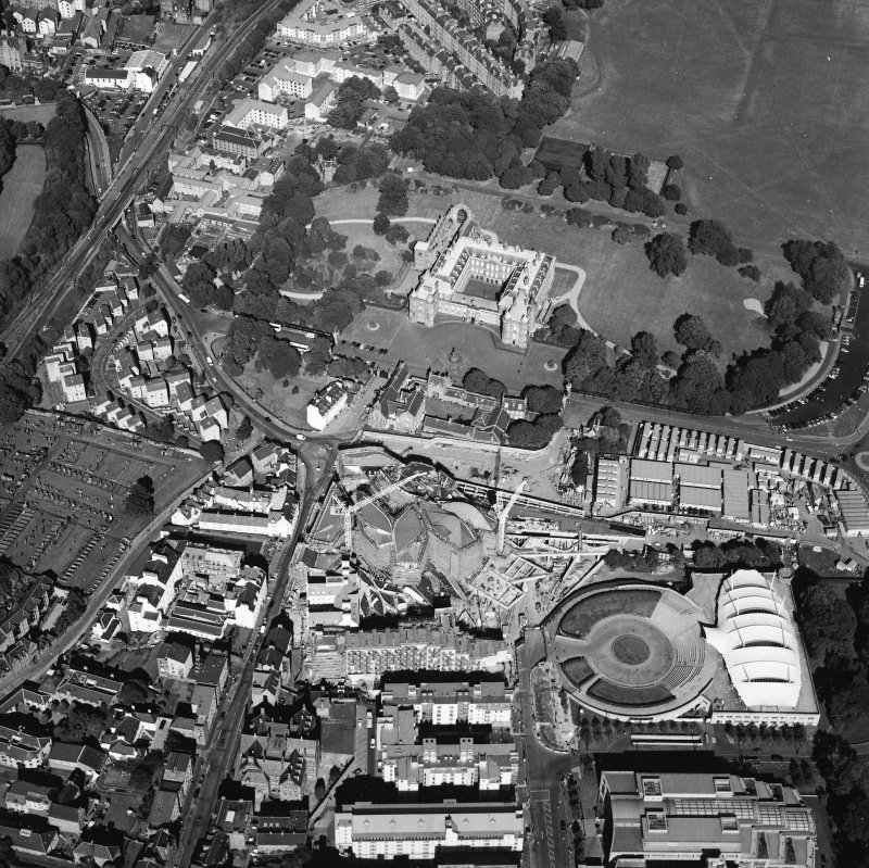 Oblique aerial view centred on the construction of the Scottish Parliament with the exhibition centre and palace adjacent, taken from the WSW.