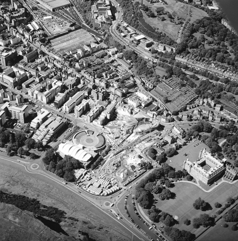 Oblique aerial view centred on the Scottish parliament building with `Our Dynamic Earth' and Holyrood palace adjacent, taken from the ESE.
