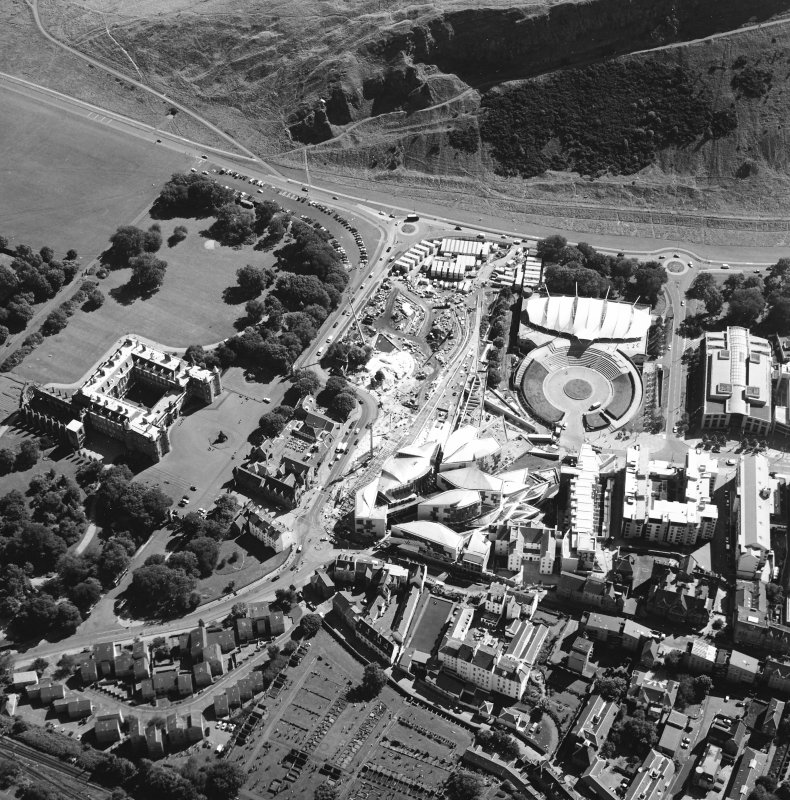 Oblique aerial view centred on the Scottish parliament building with `Our Dynamic Earth' and Holyrood palace adjacent, taken from the NW.