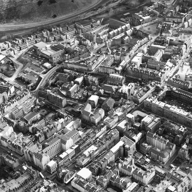 Aerial view showing South Bridge at bottom of photograph, St Mary's Street to left, Holyrood Park at top and Old College to right