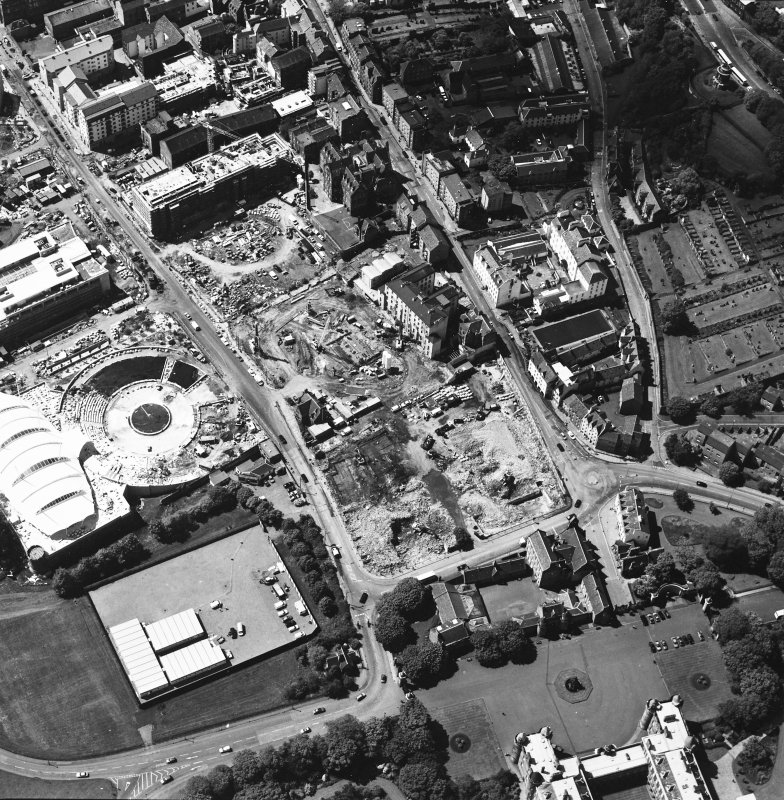 Oblique aerial view centred on the construction site, with exhibition centre and Queensbury House adjacent, taken from the SE.