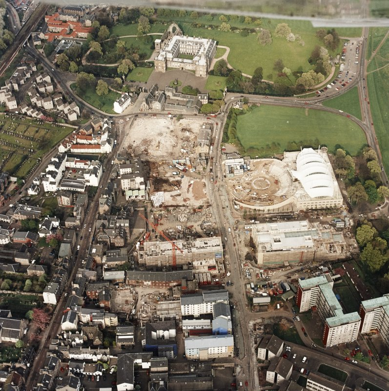 Oblique aerial view of Edinburgh centred on the construction of the Scottish Parliament with the 'Our Dynamic Earth' building and Holyrood Palace adjacent, taken from the SW.