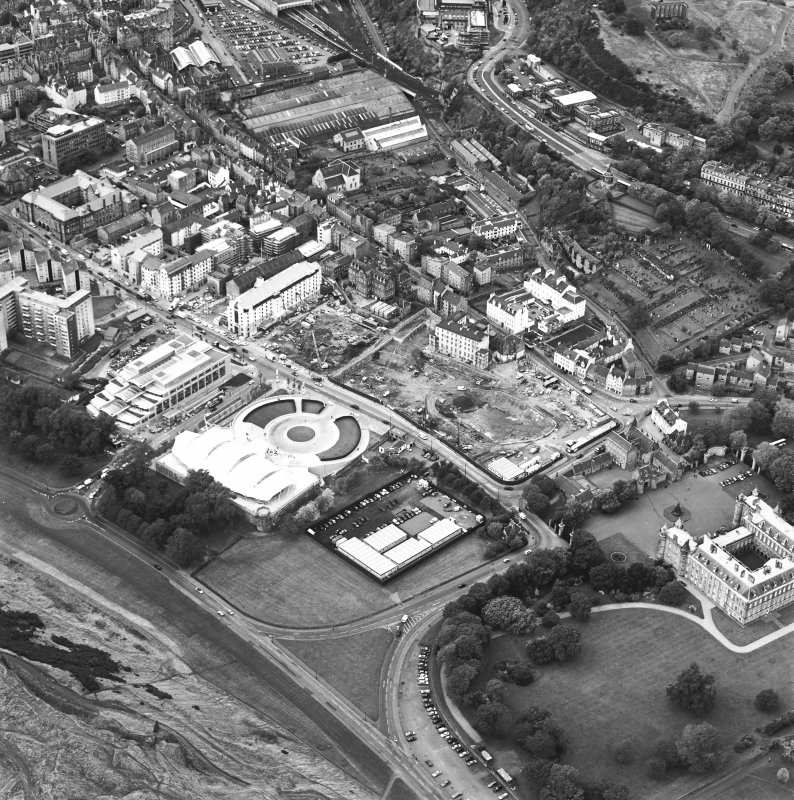 Oblique aerial view centred on the Scottish parliament under construction with `Our Dynamic Earth' and Holyrood Palace adjacent, taken from the ESE.