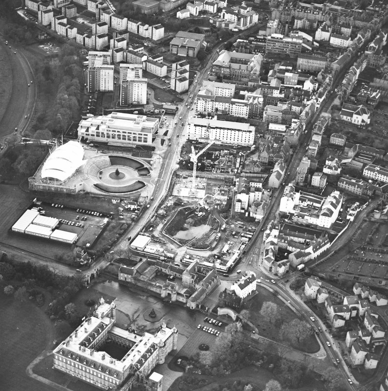 Oblique aerial view centred on the Scottish parliament under construction with `Our Dynamic Earth' and palace adjacent, taken from the NE.