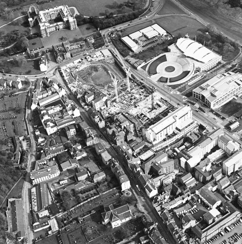 Oblique aerial view centred on the Scottish Parliament under construction with `Our Dynamic Earth¿ and palace adjacent, taken from the W.