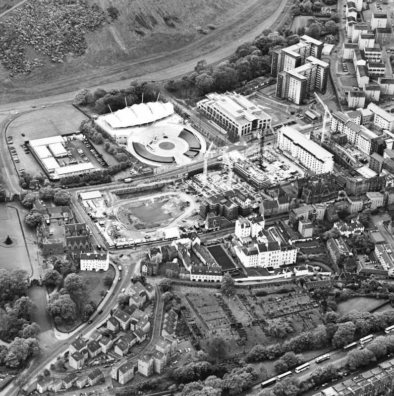 Oblique aerial view centred on the Scottish parliament under construction with `Our Dynamic Earth¿ and burial ground adjacent, taken from the NNW.