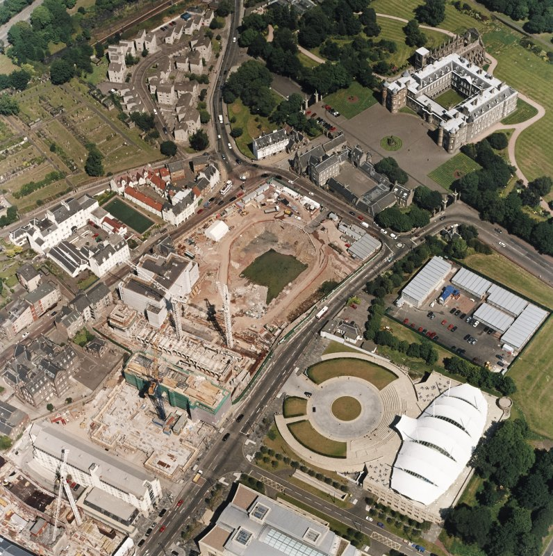Oblique aerial view centred on the Scottish Parliament under construction with 'Our Dynamic Earth' and Holyrood Palace adjacent, taken from the SW.