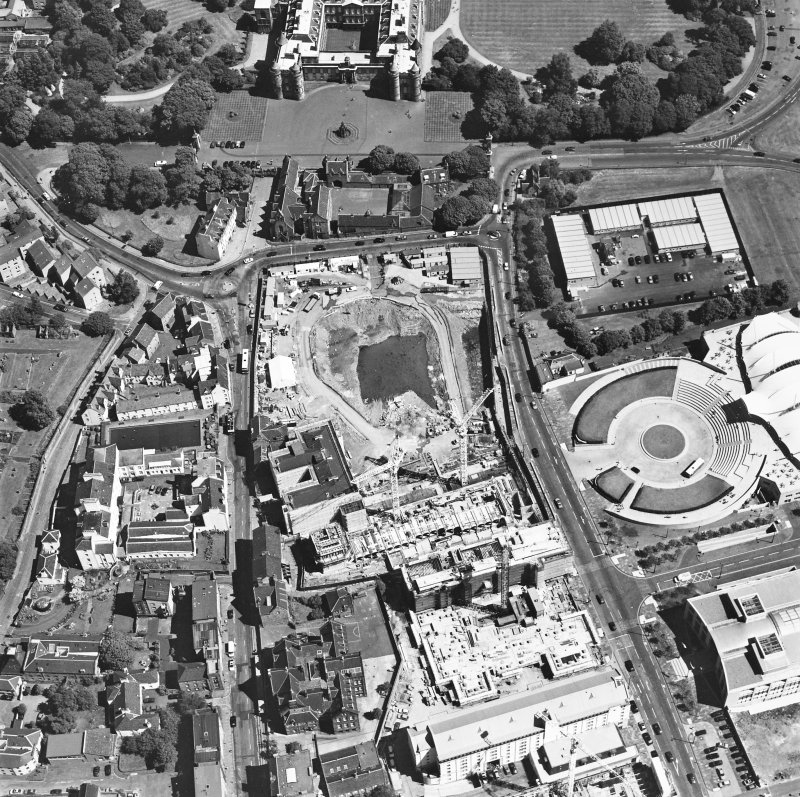 Oblique aerial view centred on the Scottish Parliament under construction with 'Our Dynamic Earth' and Holyrood Palace adjacent, taken from the WSW.