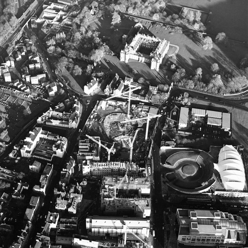 Oblique aerial view centred on the Scottish parliament under construction with `Our Dynamic Earth' and palace adjacent, taken from the SW.