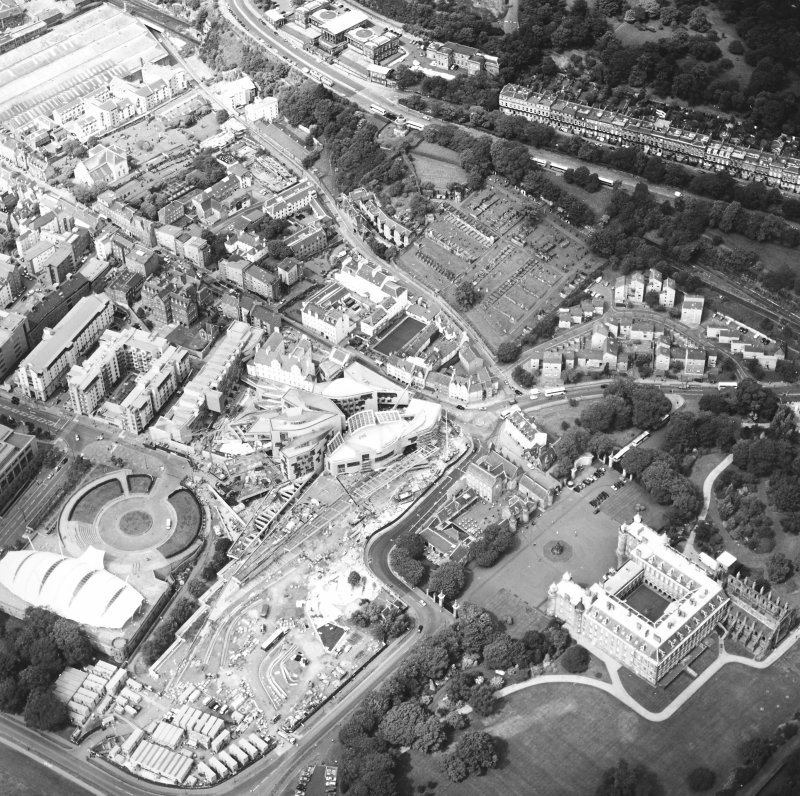 Oblique aerial view centred on the Scottish Parliament under construction with `Our Dynamic Earth' and the palace adjacent, taken from the ESE.