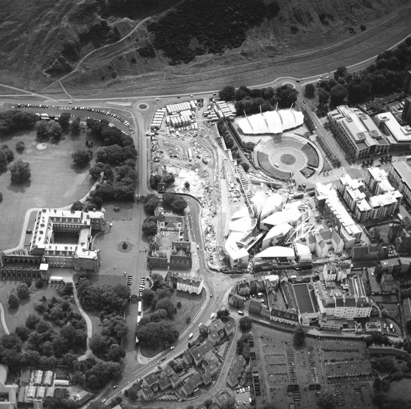 Oblique aerial view centred on the Scottish Parliament under construction with `Our Dynamic Earth¿ and the palace adjacent, taken from the NNW.