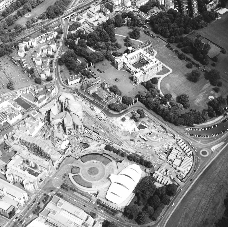 Oblique aerial view centred on the Scottish Parliament under construction with `Our Dynamic Earth¿ and the palace adjacent, taken from the SW.