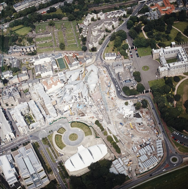 Oblique aerial view centred on the Scottish Parliament under construction with `Our Dynamic Earth¿ and the palace adjacent, taken from the S.