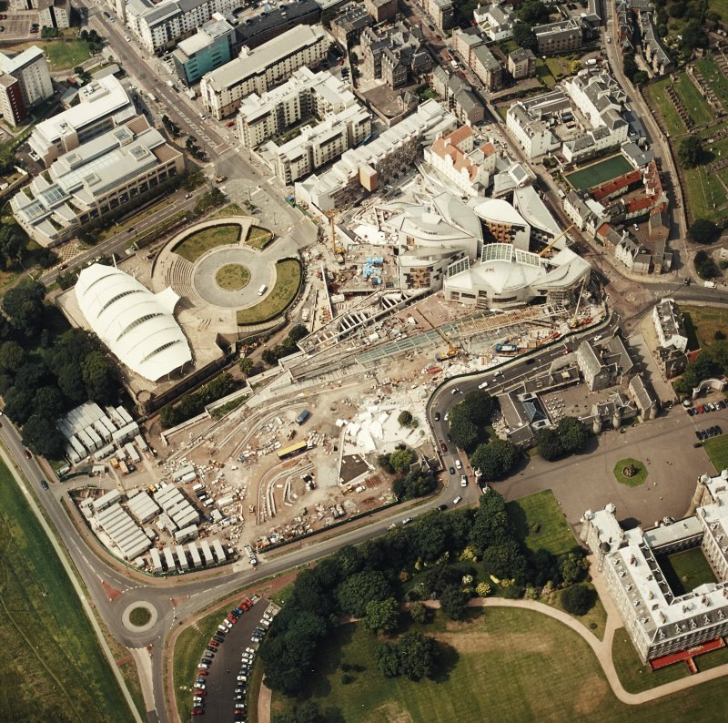 Oblique aerial view centred on the Scottish Parliament under construction with `Our Dynamic Earth¿ and the palace adjacent, taken from the E.