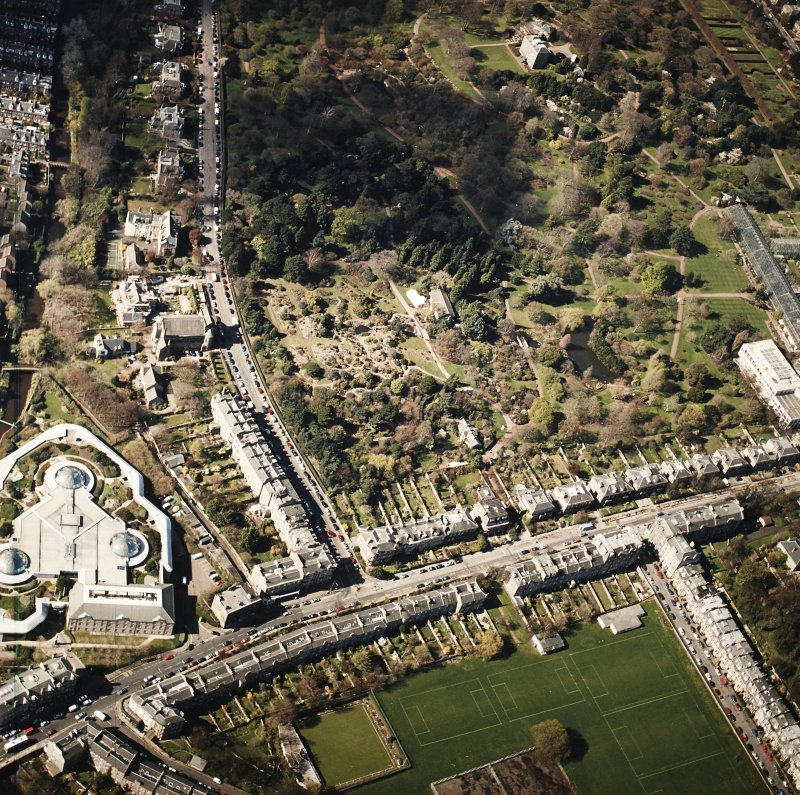 Oblique aerial view of the botanical garden centred on the Herbarium, hall and gate-lodge with the offices adjacent, taken from the ENE.
