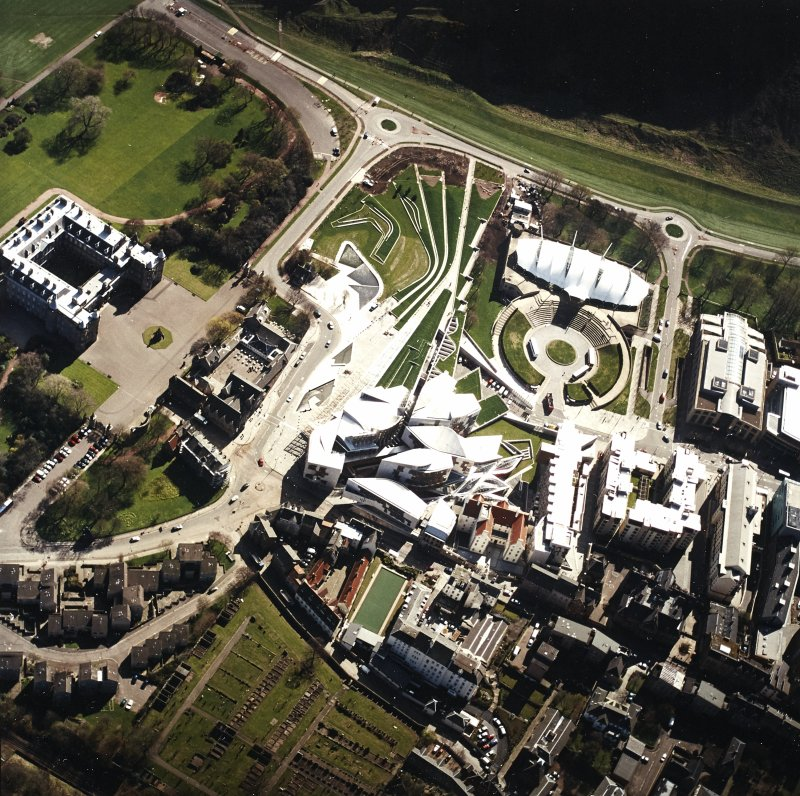 Oblique aerial view centred on the Scottish Parliament building with the exhibition centre and palace adjacent, taken from the NW.