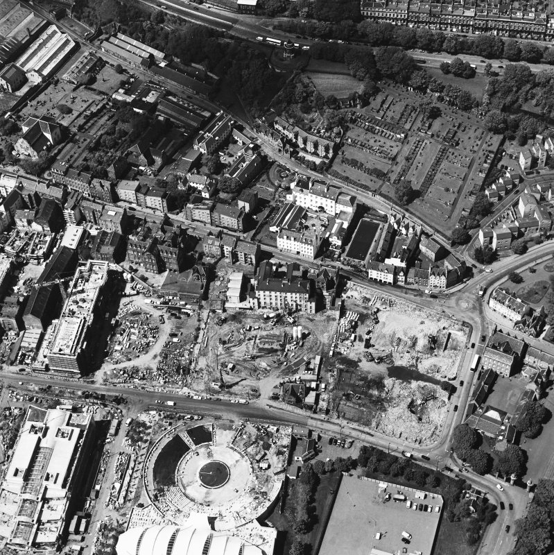 Oblique aerial view centred on the construction site, with exhibition centre and Queensbury House adjacent, taken from the S.