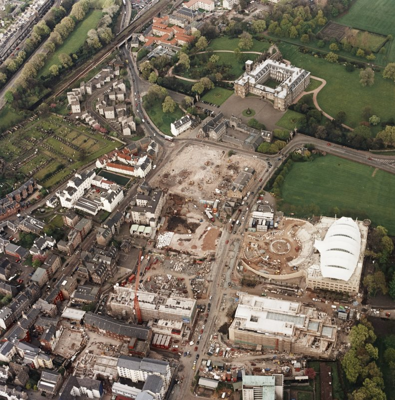 Oblique aerial view of Edinburgh centred on the construction of the Scottish Parliament with Holyrood Palace and 'Our Dynamic Earth' building adjacent, taken from the SW.