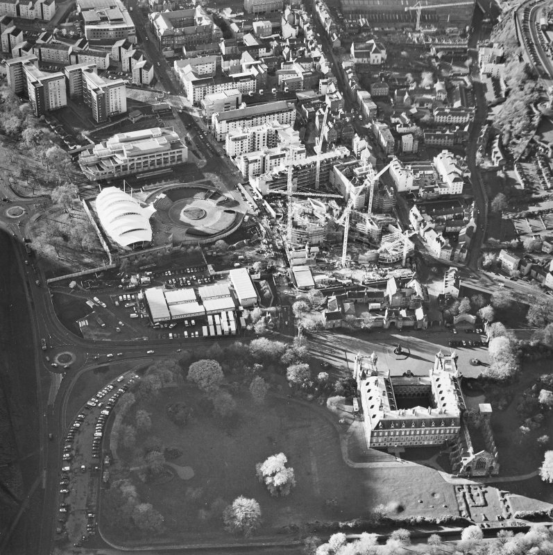 Oblique aerial view centred on the construction of the Scottish Parliament with the exhibition centre and palace adjacent, taken from the ENE.