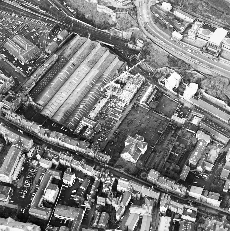Oblique aerial view centred on the development of Tolbooth Wynd with the church and graveyard adjacent, taken from the SE.