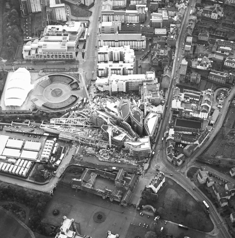 Oblique aerial view centred on the construction of the Scottish Parliament with exhibition centre adjacent, taken from the ENE.