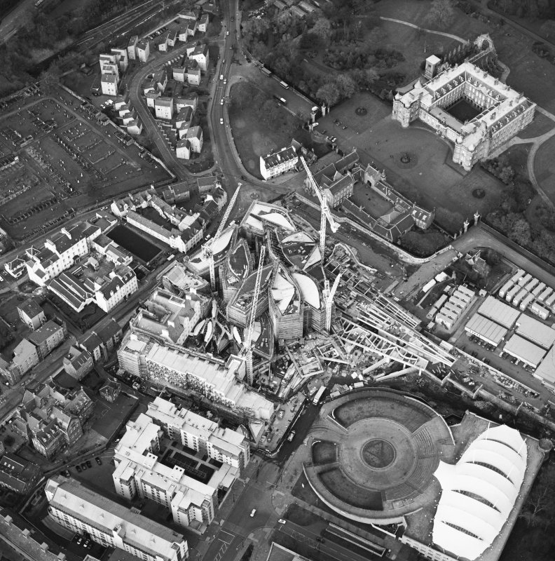 Oblique aerial view centred on the construction of the Scottish Parliament with exhibition centre and palace adjacent, taken from the SSW.