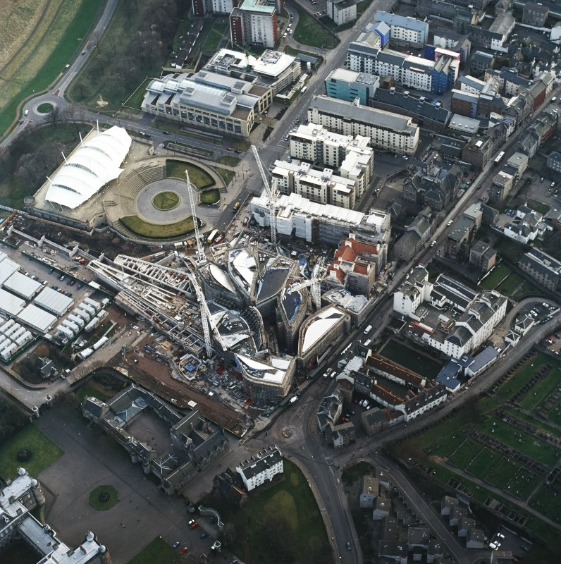 Oblique aerial view centred on the construction of the Scottish Parliament with exhibition centre adjacent, taken from the NE.