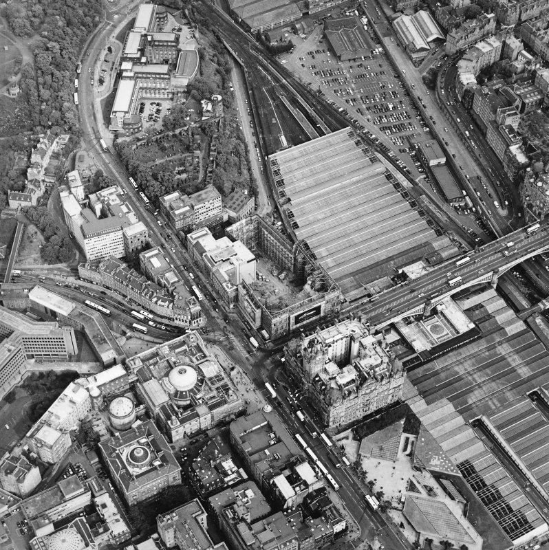 Oblique aerial view centred on the redevelopment of the former post office, with the register house under repair and the railway station and hotel adjacent, taken from the WNW.