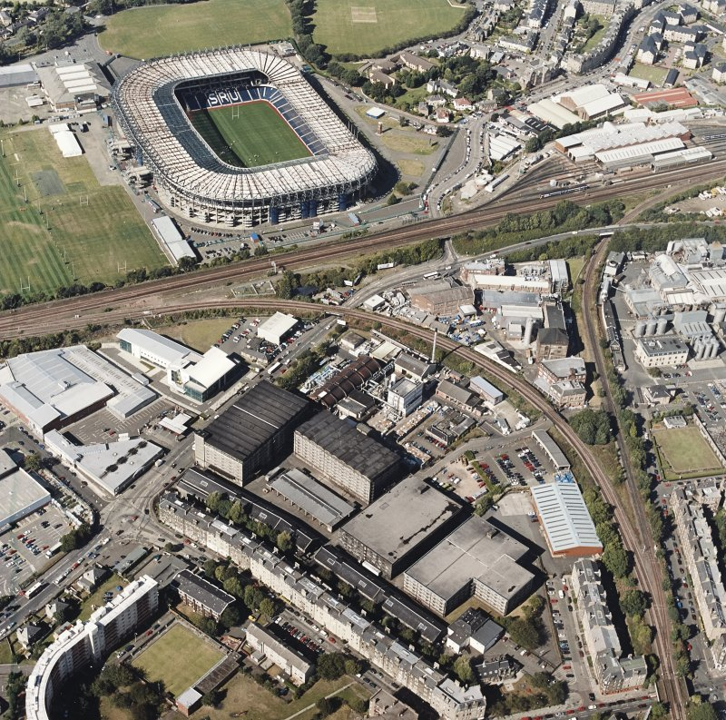 Oblique aerial view centred on the bonded warehouse with the park and bowling green and stadium adjacent, taken from the S.