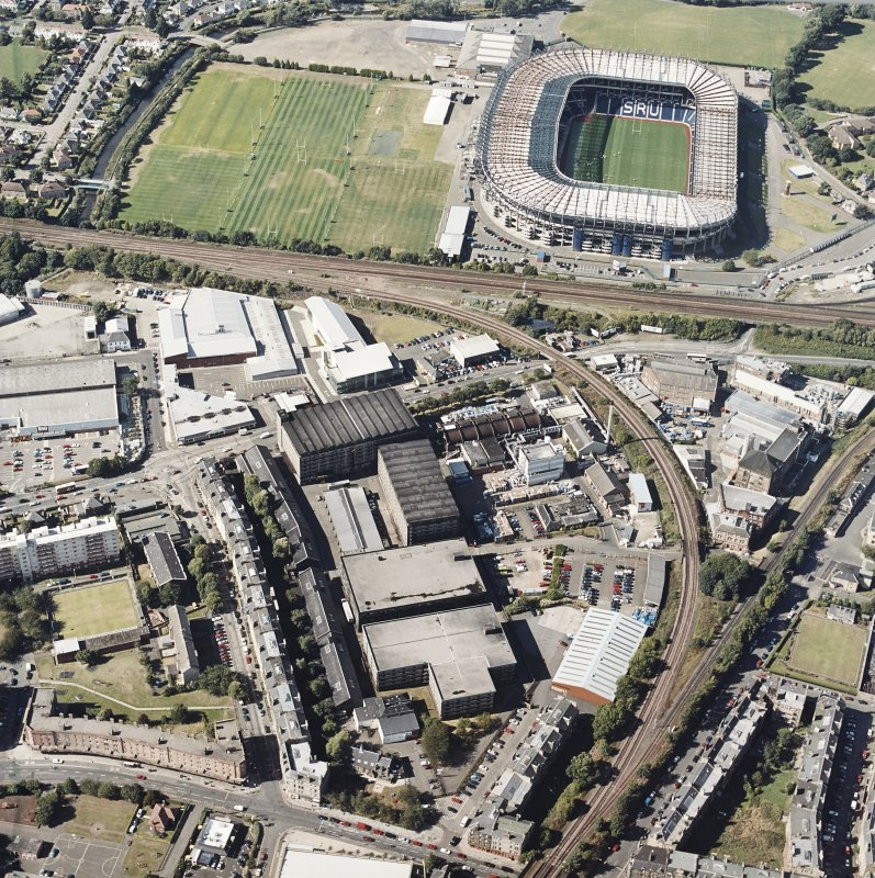 Oblique aerial view centred on the bonded warehouse with the park and bowling green and stadium adjacent, taken from the SSE.