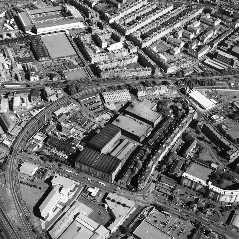 Oblique aerial view centred on the bonded warehouse with the park and bowling green and the football stadium adjacent, taken from the W.