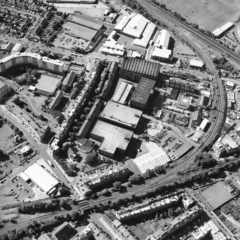 Oblique aerial view centred on the bonded warehouse with the park and bowling green adjacent, taken from the ESE.