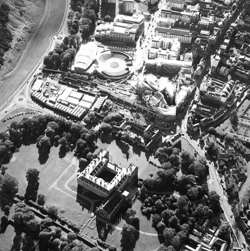 Oblique aerial view centred on the construction of the Scottish Parliament with the exhibition centre and palace adjacent, taken from the NE.