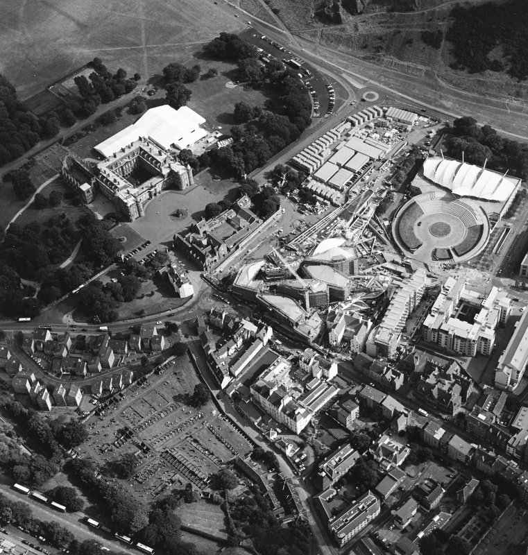 Oblique aerial view centred on the construction of the Scottish Parliament with Our Dynamic Earth, Queensbury House and Holyrood Palace adjacent, taken from the NW.