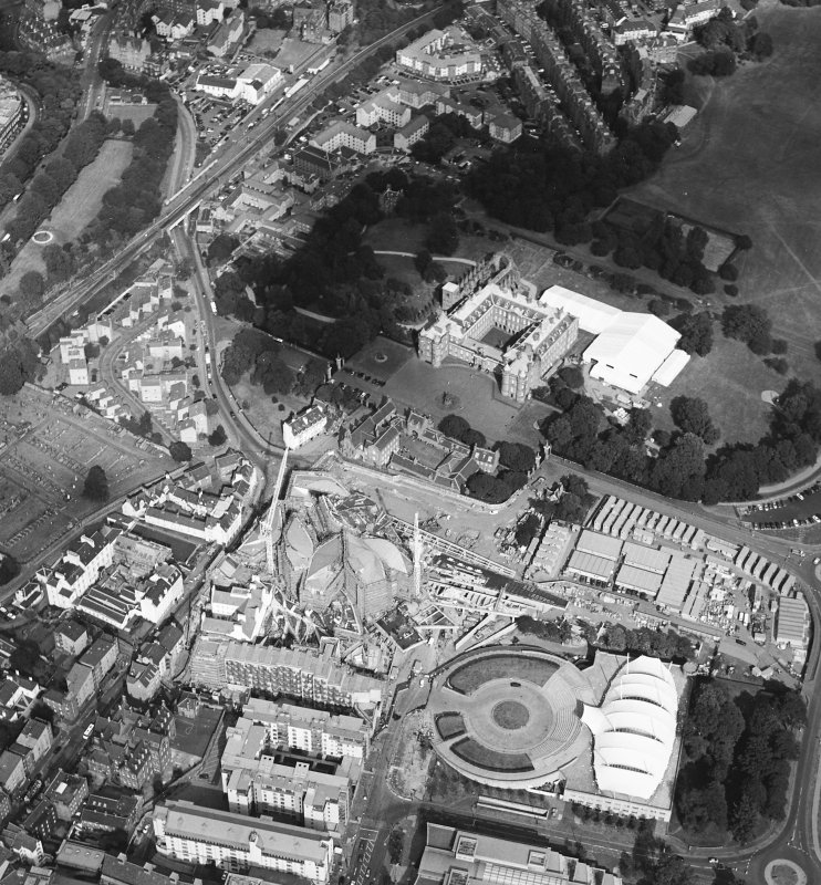 Oblique aerial view centred on the construction of the Scottish Parliament with Our Dynamic Earth, Queensbury House and Holyrood Palace adjacent, taken from the SSW.