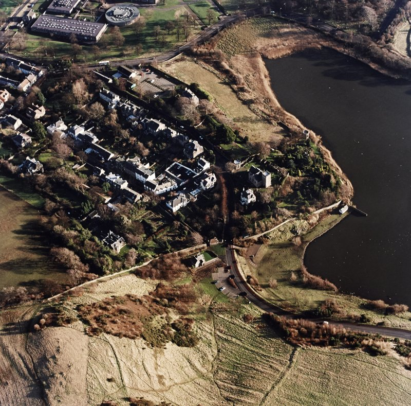 Oblique aerial view of Edinburgh centred on Duddingston Village with the parish church and south lodge visible, taken from the NW.