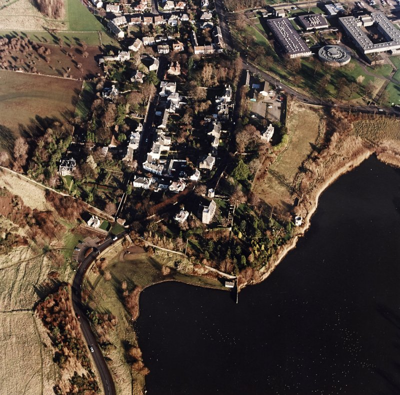 Oblique aerial view of Edinburgh centred on Duddingston Village with the parish church and south lodge visible, taken from the WSW.