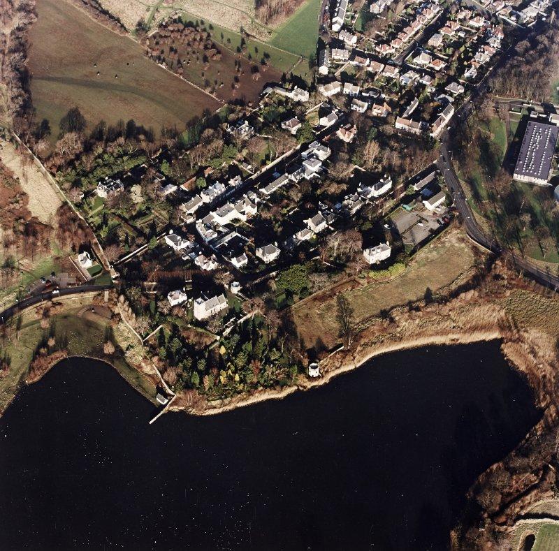 Oblique aerial view of Edinburgh centred on Duddingston Village with the parish church and south lodge visible, taken from the SW.