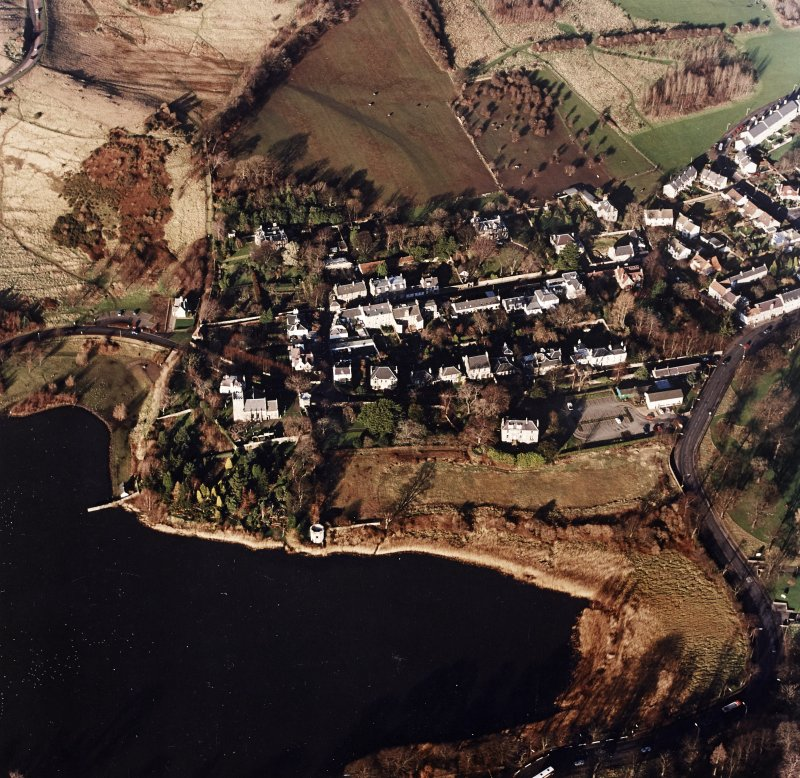 Oblique aerial view of Edinburgh centred on Duddingston Village with the parish church and south lodge visible, taken from the S.