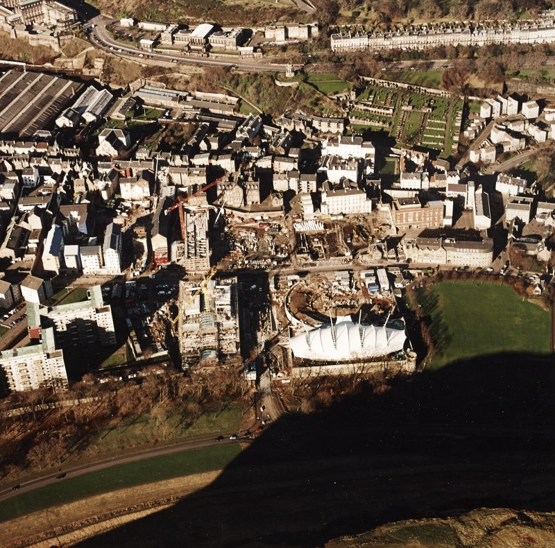Oblique aerial view centred on the Scottish parliament under construction with 'Our Dynamic Earth' adjacent, taken from the SE.