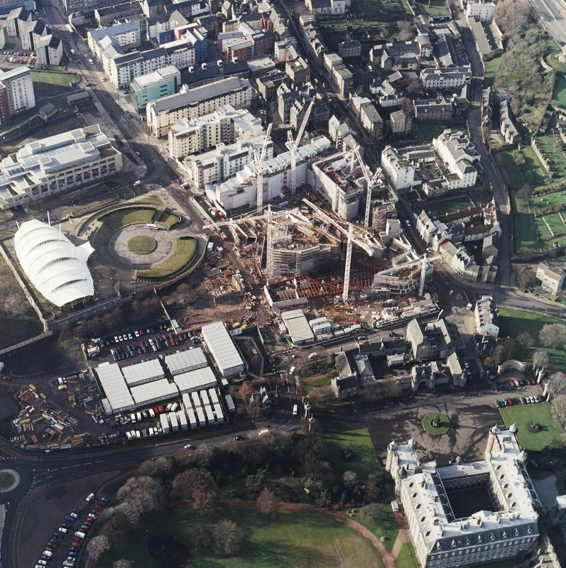 Oblique aerial view centred on the construction of the Scottish Parliament, with `Our Dynamic Earth¿, Queensberry House and Holyrood Palace adjacent, taken from the E.
